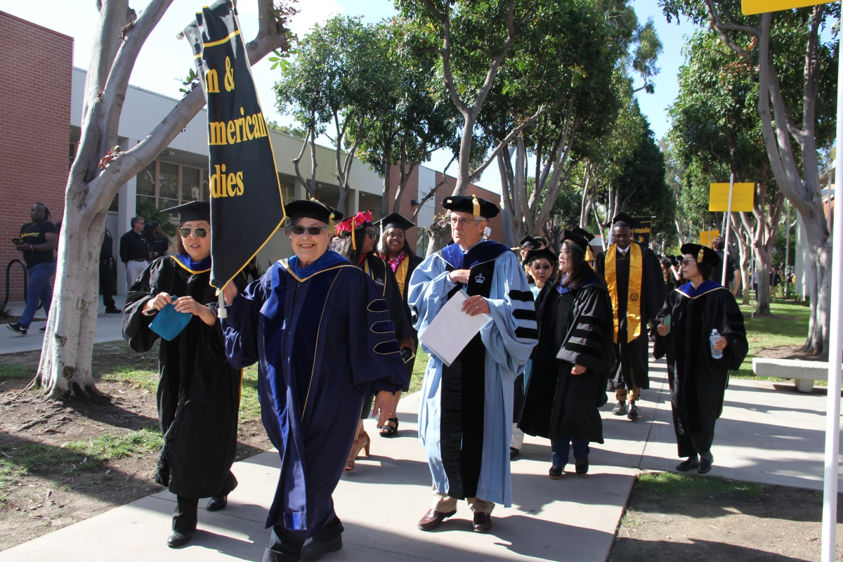AAAS department walking to commencement with banner.