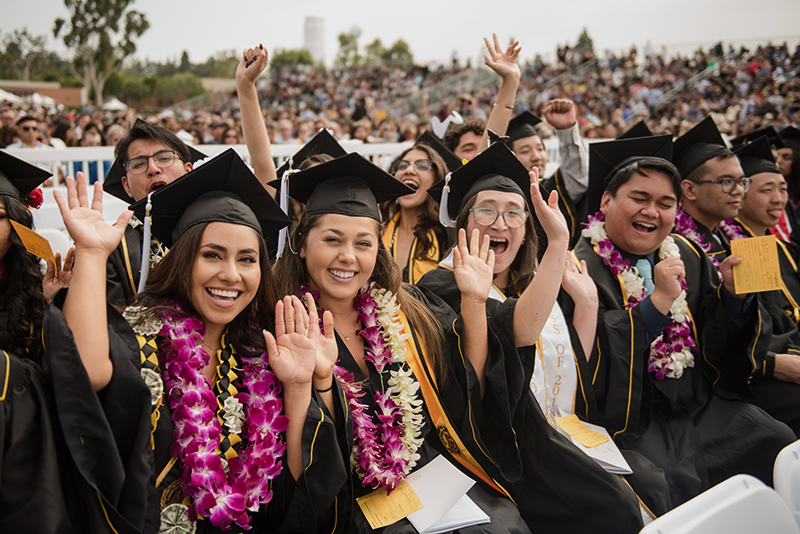 Group of students smiling and waving at Commencement